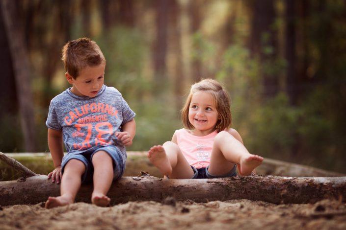 lachende kinderen spelen in het bos