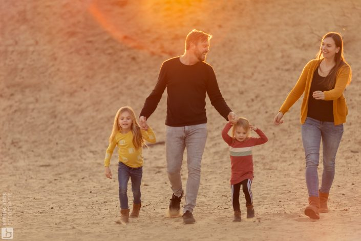gezin wandelt over zandvlakte