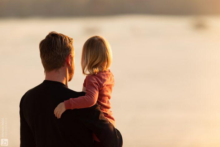 vader kijkt met kind naar de ondergaande zon