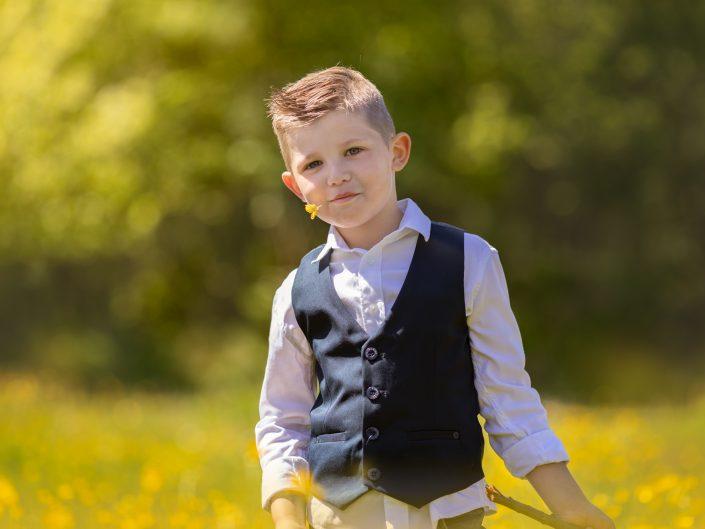 Jongen met gele bloemen Familie fotoshoot Belevenissenbos Zuigerplasbos Lelystad